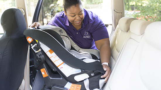Lauren Brown, certified car seat tech, installs car seat for patient family