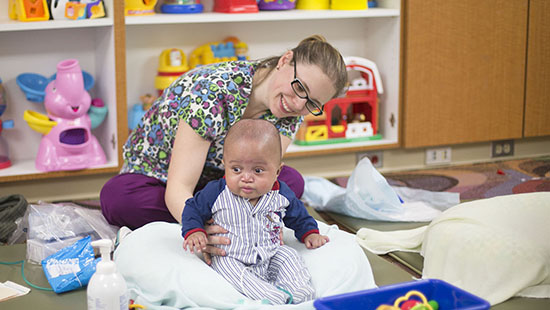 Nurse with patient in our infant playroom