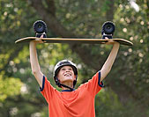 Allied Health jobs image of a kid wearing a helmet and holding a skateboard over their head